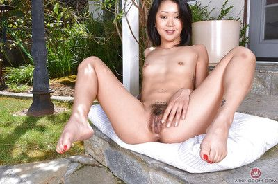 Asian first timer Saya Song showing off hairy bush on concrete steps
