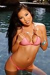Wet round boobed asian babe Thuy Li poses in revealing pink bikini in the sun
