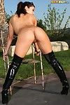 Japanese sexbomb Akira Lane dressed in high boots displays her big tits and shaved pussy outdoors