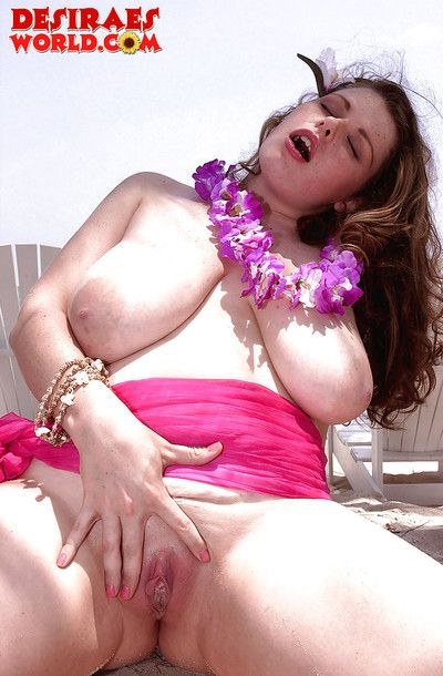 Chubby MILF pornstar sets free heavy saggy breasts outdoors on beach