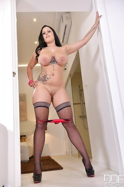 Darksome haired heavy Themis Thunder revealing massive hooters and tattoos