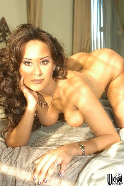 The stripped Asian beauty Asia Carrera is playing with her giant boobs on camera
