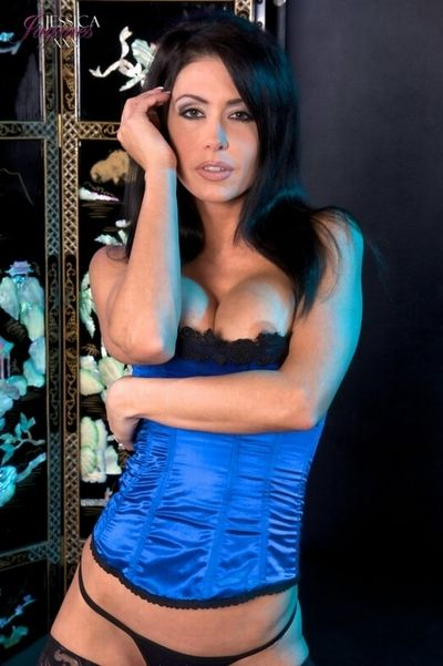 Big titted Jessica Jaymes in corset stretches legs in fishnet stockings and shows naked pussy