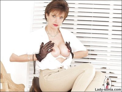 Fully-clothed mature fetish lady uncovering her tits and changing her boots