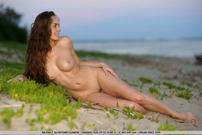 Fully nude brunette Milana F with shapely tits and shaved pussy poses at the seaside