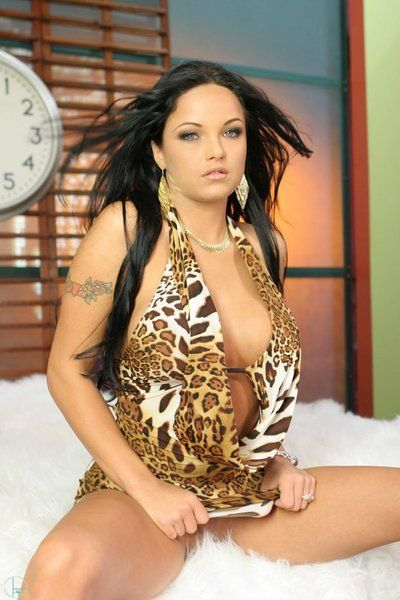 Raven haired bombshell Lanny Barbie in sexy leopard dress shows off her big tits and bald twat