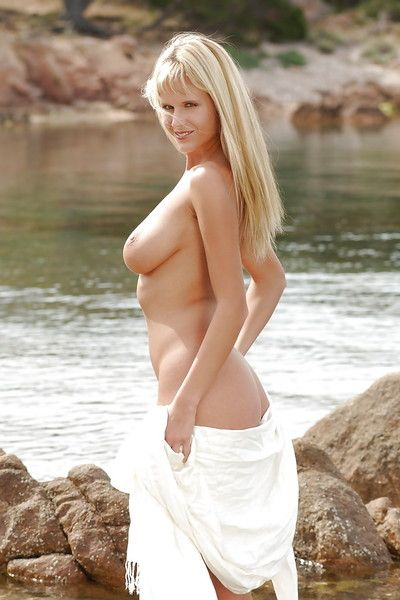 Sexy pornstar babe disrobes on the shore and shows comely melons