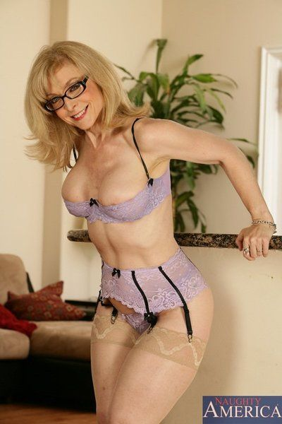 Leggy blonde milf Nina Hartley in glasses poses in lingerie then takes care of thick solid cock