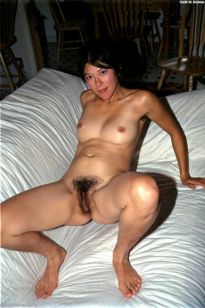 Amateur Asian cutie Amanda lies on big couch and spreads her hairy chinchilla