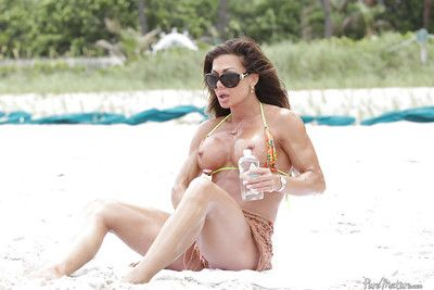 Mature woman Nina Dolci letting firm tits free from bikini on beach