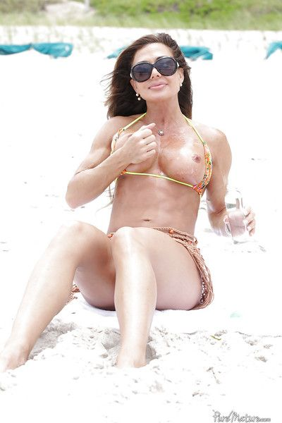 Mature woman Nina Dolci letting firm tits free from bikini on beach