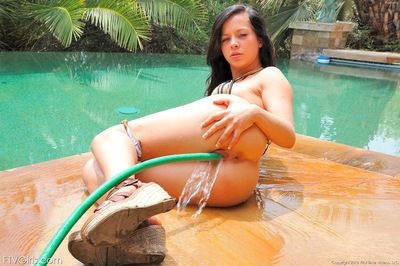 Sweet brunette wanking her skinhead pussy with the water hose