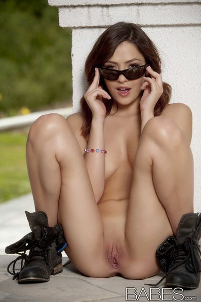 Young beauty removing her appealing bikini in outdoor solo session