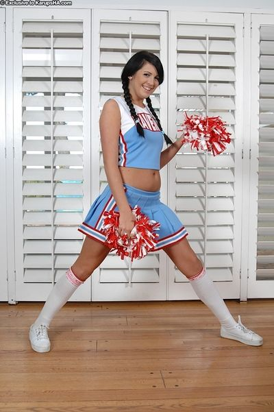 Black haired cheerleader Skyla Paige in blue uniform and panties divulges her smooth on top cum-hole