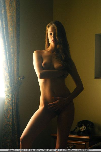 Swarthy haired ukrainian kitty Vika Ac poses undressed in the semi darkish of the bedroom