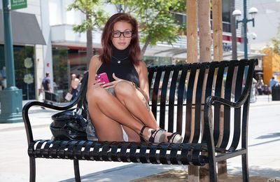 Young doll with untamed glasses unfolds her underclothes in public teasing with that arse