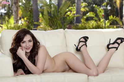 Young Cassie Laine in high heels takes off her lingerie and touches her hairless snatch