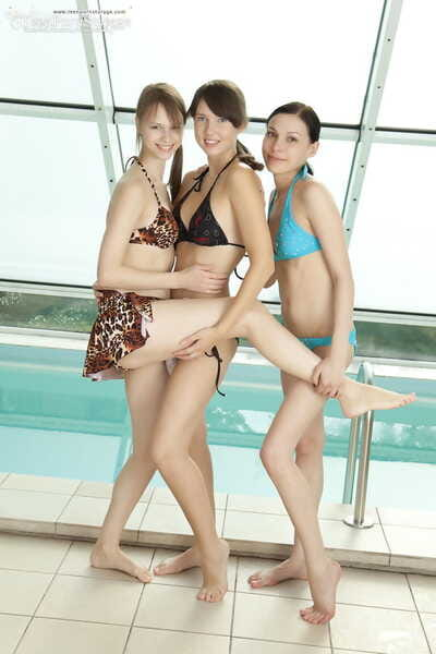 3 leggy legal age teenagers takes off their bikinis to pose uncovered next to an indoor pool