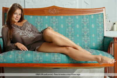Young redhead with long hair and legs Angelina B disrobes for unclothed shoot