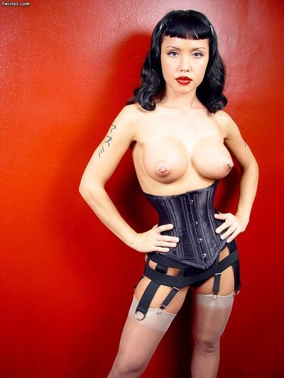 Chinese lass Masuimi Max standing in fixed leather corset and shows her stripped boobs.