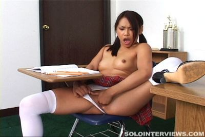 Oriental schoolgirl Veronica Lynn in white shorts and red plaid petticoat rubs her vagina