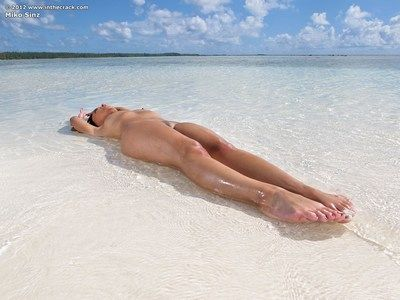 Seductive Eastern beauty Miko Sinz shows her bald tacky wet crack on the beach